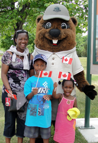 Parka poses with a mother and her two young kids as they wave Canadian flags.