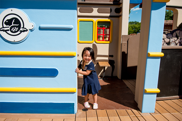 Smiling girl standing at the entrance of the passenger car of the train