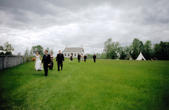 Wedding party walking across historic grounds