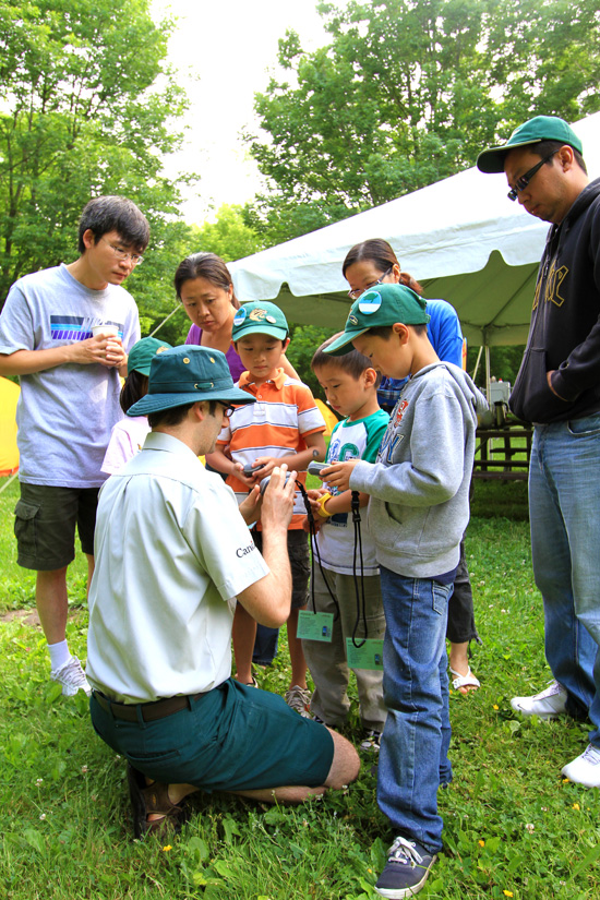 Geordan teaches the young campers how to use the GPS devices before starting to Geocache.