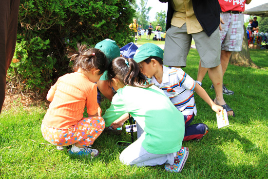 The junior Geocachers excitedly search through the cache for their prizes.