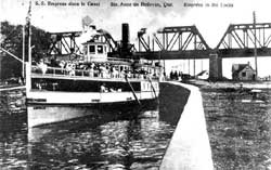 The S.S. Empress with many passengers on the bridge leaving the Sainte-Anne-de-Bellevue lock towards the Ottawa River. In the background, a railway bridge.