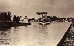 Steamboat entering the Becker dam. To the left, a small lighthouse. In the background, the town of Sainte-Anne-de-Bellevue, 1910.