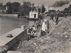 Seventeen workmen rebuilding a dock in the Chambly Canal in Saint-Jean-sur-Richelieu.