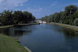 View of boats entering lock number 5 from lock number 6. Multipurpose trail to the right of the canal.