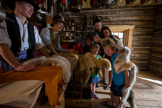 A boy has a coyote fur draped over his shoulders and head in the trading post while family members and two costumed staff members look on.