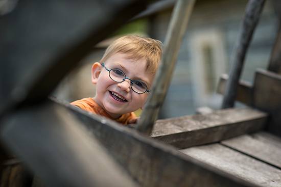 A small boy with glasses shows a big grin as he looks between the spokes of a red river cart.