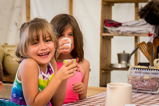 Two small girls are laughing as they hold and drink from cups in their hands.