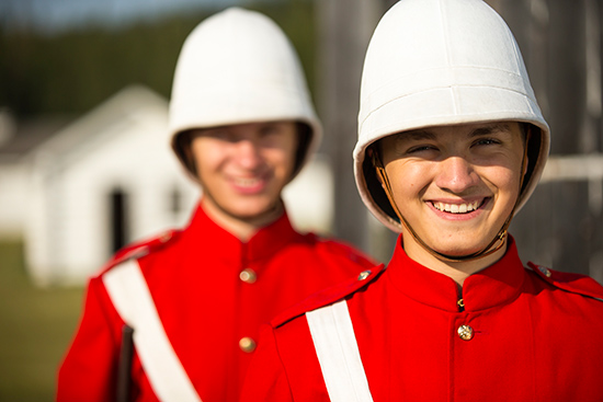 Head and shoulder shot of two smiling NWMP members dressed in red surge.