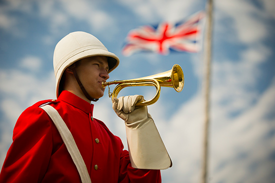 A uniformed NWMP officer in red surge with a pith helmet plays a bugle while a Union Jack flag flies in the background.