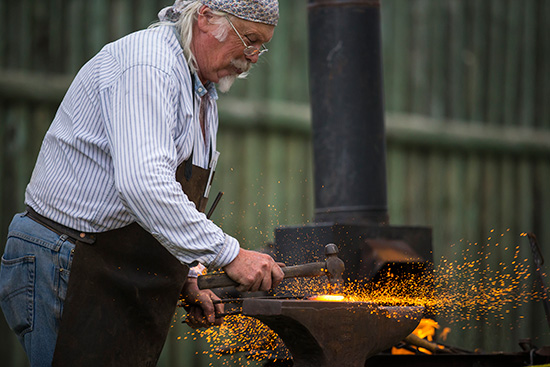 A blacksmith hammers hot metal on an anvil creating sparks.