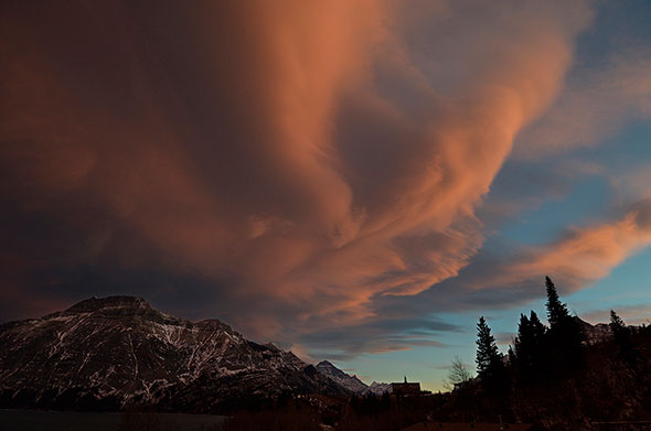 A chinook arch is lit up as the sun goes down in Waterton in late November