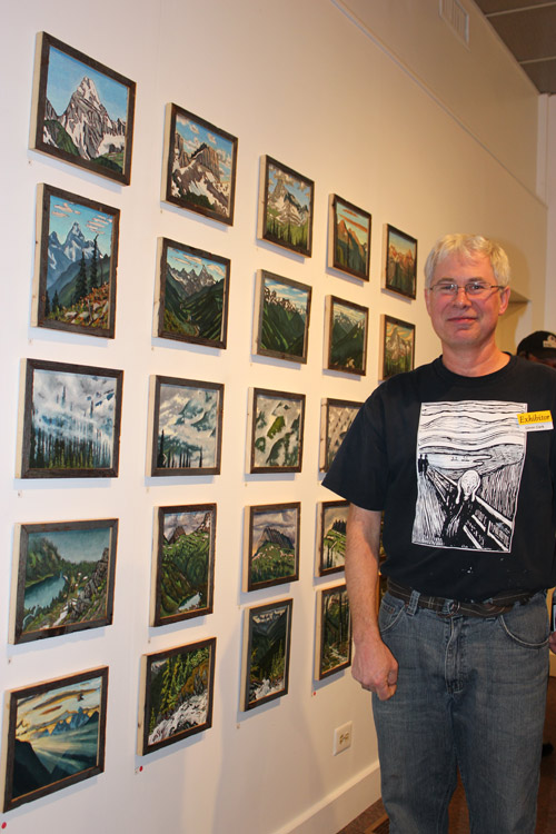 Glenn Clark beside a grouping of 25 of his paintings