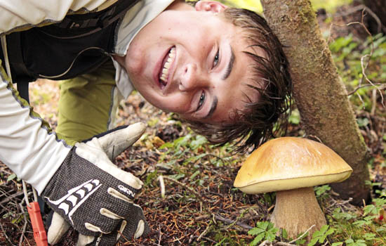 Student posing with a mushroom, giving a thumbs-up