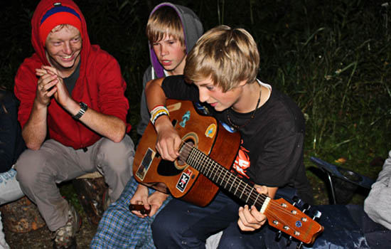 A student playing guitar by a campfire while two other students watch