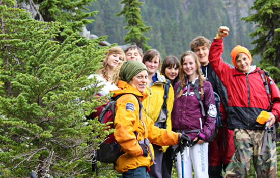 A group of students hiking in sub-alpine trees