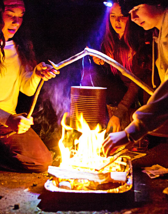 Three students boiling water in a can over a campfire