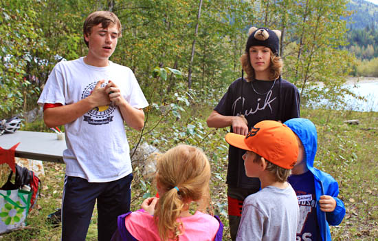 Two students explaining an activity to a group of children