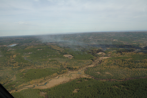 Aerial view of burn area showing smoke
