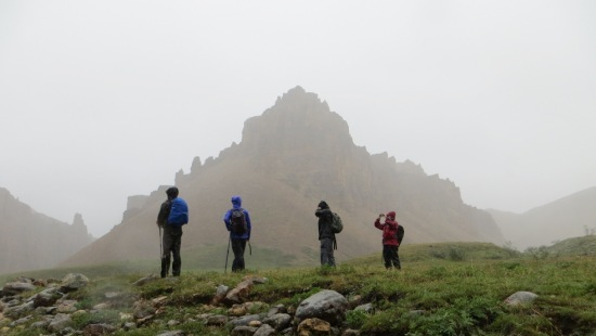 Four hikers stop in the fog to take some photos