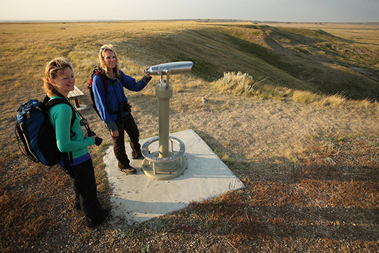 Two women enjoy the view from the telescope lookout along the Top Dog Trail.