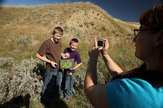 Two boys have their photo taken after finding a geocache.
