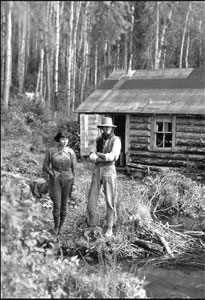 Old picture of a man and a woman in front of log cabin