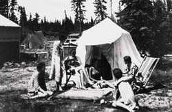 Archival photo of six people camping with a canvas bell tent.