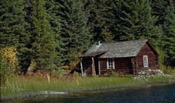 Cabin of naturalist Grey Owl viewed from lake summer.
