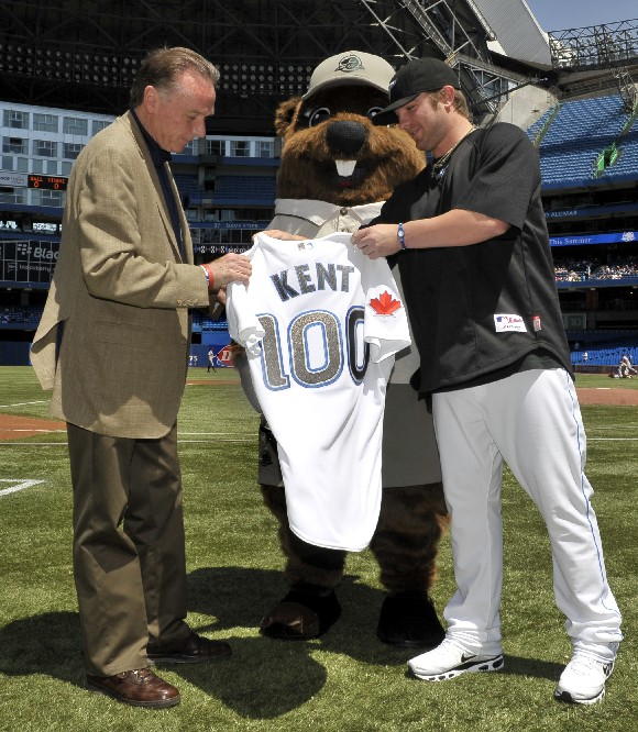 Minister Kents accepts a honourary team jersey, before throwing out the first pitch at a Toronto Blue Jays game to celebrate Parks Canada centennial, at the Rogers Centre, in Toronto.