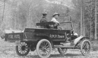 Old fire truck with two men on a dirt road with trees and mountains in the background.