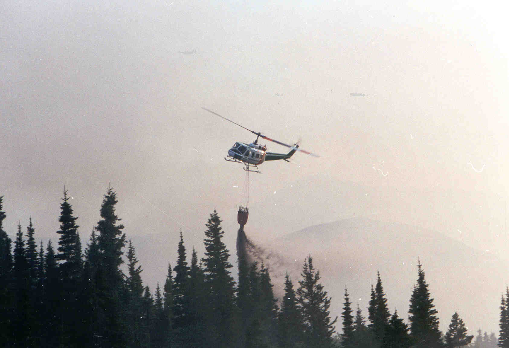 A helicopter dropping a bucket full of water on a fire