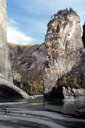 Picture of rock formation which looks like a medieval tower,the Pulpit Rock. At the foreground, the South Nahanni River.