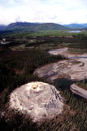 Picture of singular geological feature which would look like a gigantic wasps' nest followed by all round stretches of water it is the Rabbitkettle hotspring. All around, the forest and the mountains in the background.