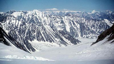 An aerial view of mountains including Mount Logan with snow flow at the forefront.