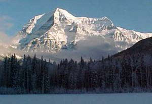 The majestic mount Robson in the provincial of the same name. At the foreground water and a forest.