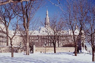 Picture of of Québec seminary in winter. A few trees at the foreground.