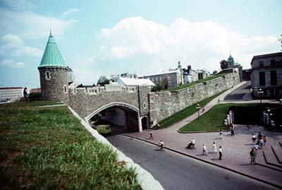 Picture of the St-Jean Gate and Québec fortifications from the wall of the fortifications. A few tourists a walking around.