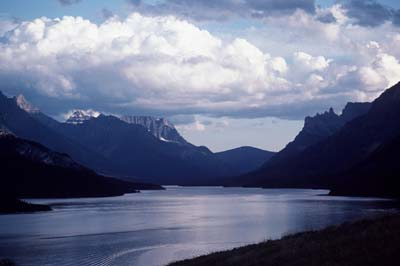 Waterton Lake towards Glacier National Park in the United States. Lake, mountains and cloudy sky.