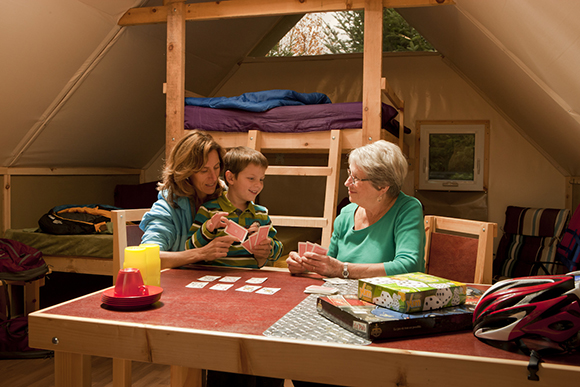A family playing a board game on the table inside an oTENTik tent.
