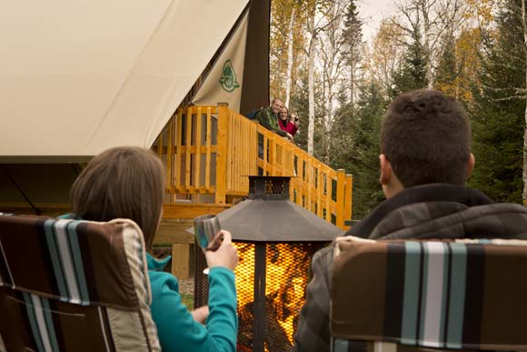 A couple seen from the back is sitting in front of a campfire while another couple is standing in the background on the oTENTik tent's balcony, looking at them.