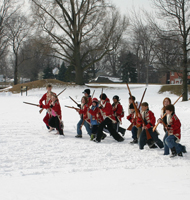 Children dressed as soldiers run in the snow.